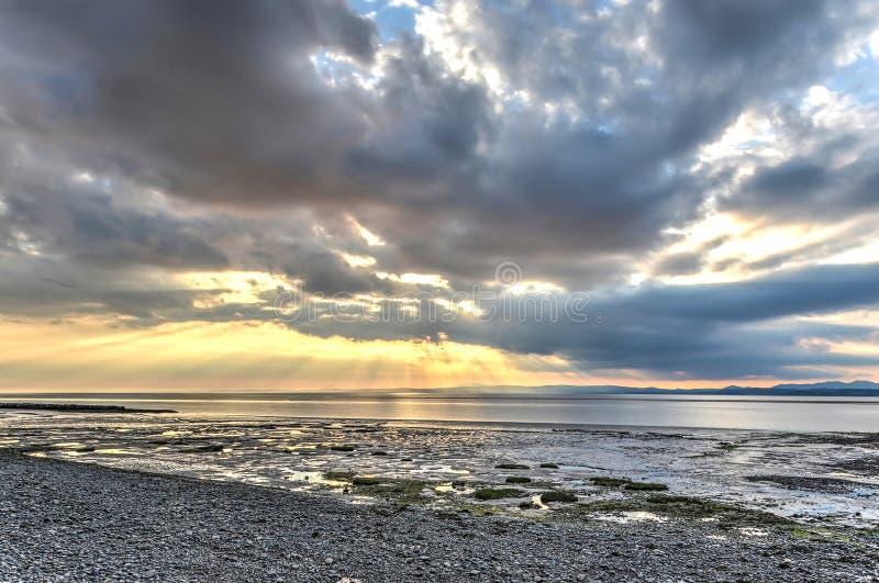 Låg sol som bryter till och med molnen på Morecambe royaltyfri foto
