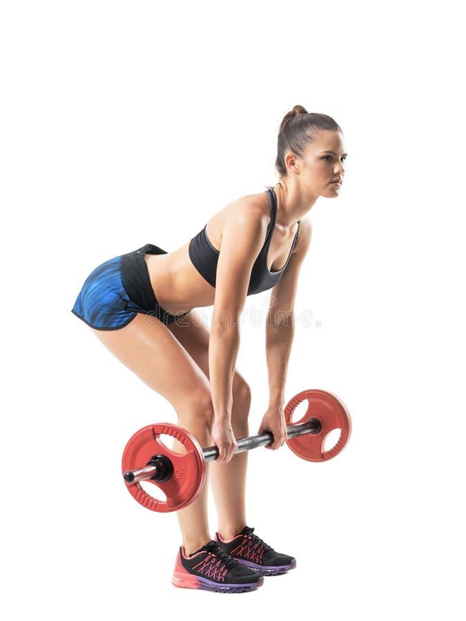 Låg startposition av den kvinnliga idrottsman nen för krökning som gör deadliftövning med skivstångprofil fotografering för bildbyråer