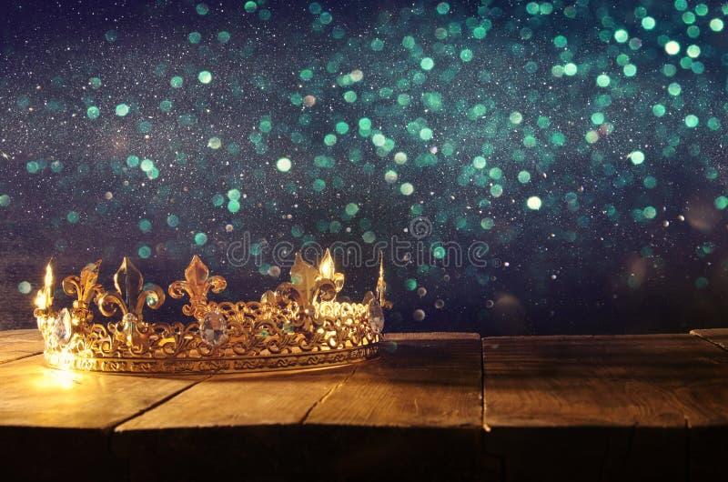 låg tangent av den härliga drottning-/konungkronan över trätabellen Filtrerad tappning medeltida period för fantasi arkivfoton