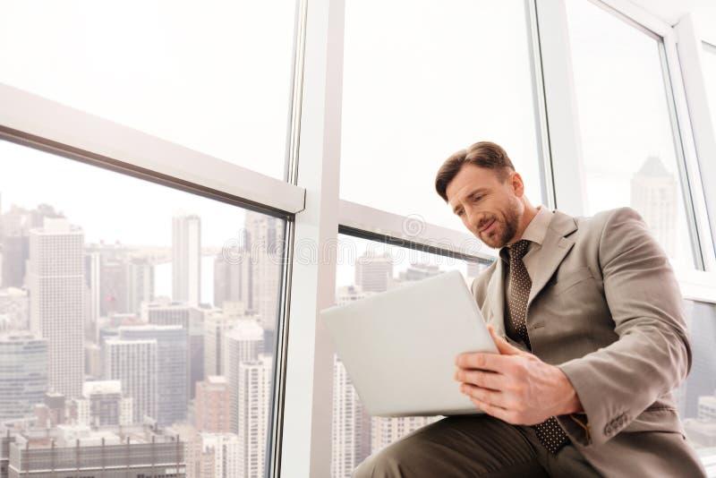 Låg vinkel av den allvarliga affärsmannen som använder bärbara datorn arkivfoton