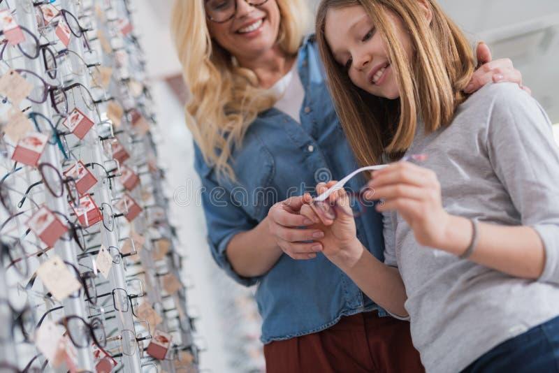 Låg vinkel av en angenäm flicka och hennes moder som väljer exponeringsglas arkivbild