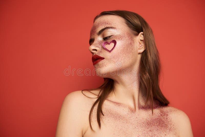 L?g vinkel av flickan med id?rik makeup och denformade klisterm?rken p? framsida arkivfoton