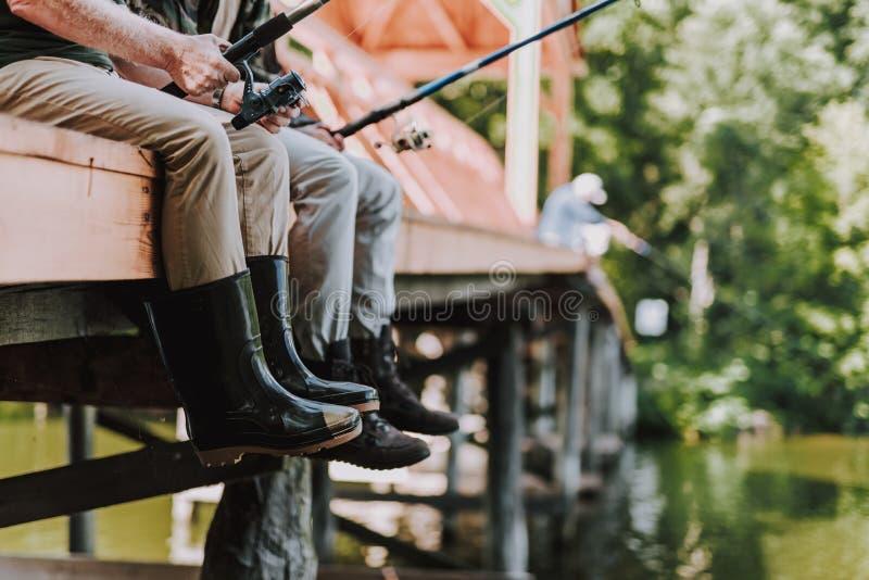 Låg vinkel av manliga sportfiskare i kängor royaltyfri fotografi