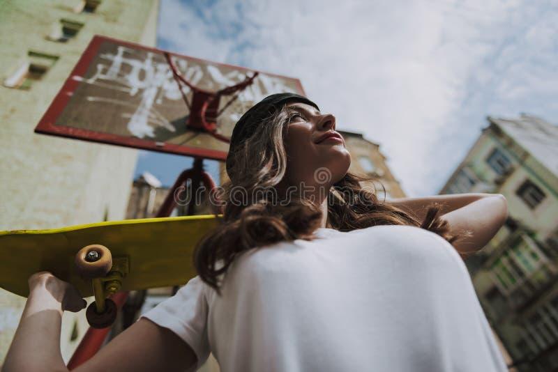 Låg vinkel som ler flickan med den gula skateboarden arkivfoto