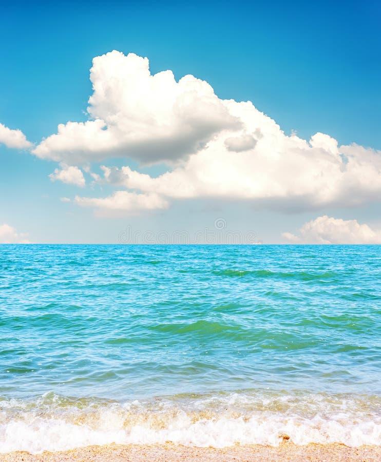 låga moln i blå himmel över havs- och sandstranden royaltyfria bilder