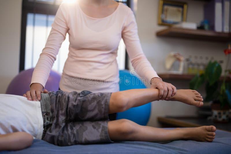 Lågt avsnitt av pojken som undersöks av den kvinnliga terapeuten arkivbild