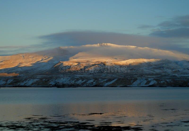 Lågt berg under snö som döljas i moln royaltyfri foto