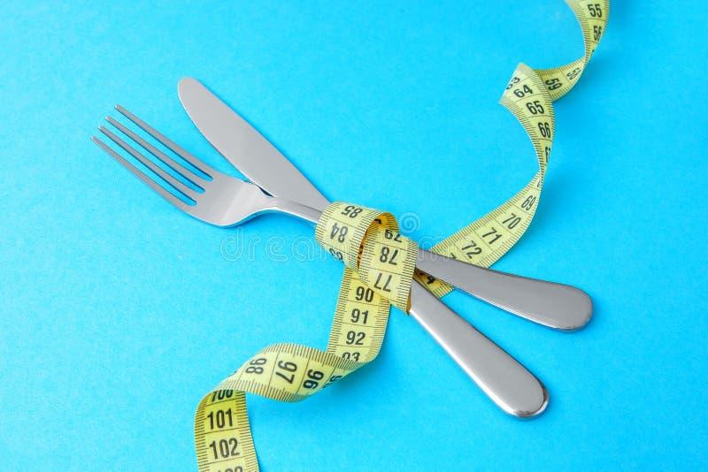 Lågt - kalorin bantar för viktförlust Gaffeln och kniven slås in i gult mäta band på blått royaltyfri fotografi