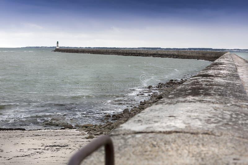 Lågvattenlandskap med fyren ett litet fartyg för D i Le Croisic royaltyfri bild