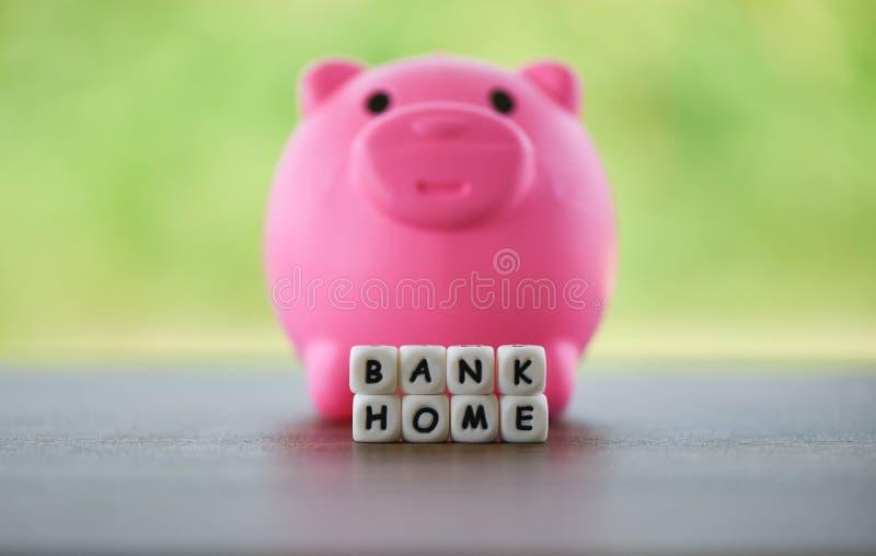 Lån för besparingar för fastighetförsäljningshem marknadsför begreppsrosa färgspargrisen och tärnar ord av bankhemmet royaltyfri fotografi