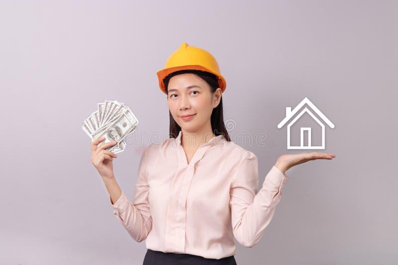 Lån för fastighetbegrepp, kvinna med gula pengar för hjälminnehavsedel i hand och vit logohemsymbol i en annan hand royaltyfri bild