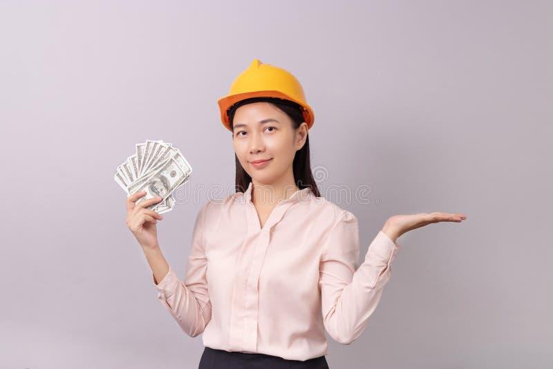 Lån för fastighetbegreppet, kvinna med gula pengar för hjälminnehavsedeln i assistent och att öppna det tomt gömma i handflatan royaltyfri bild