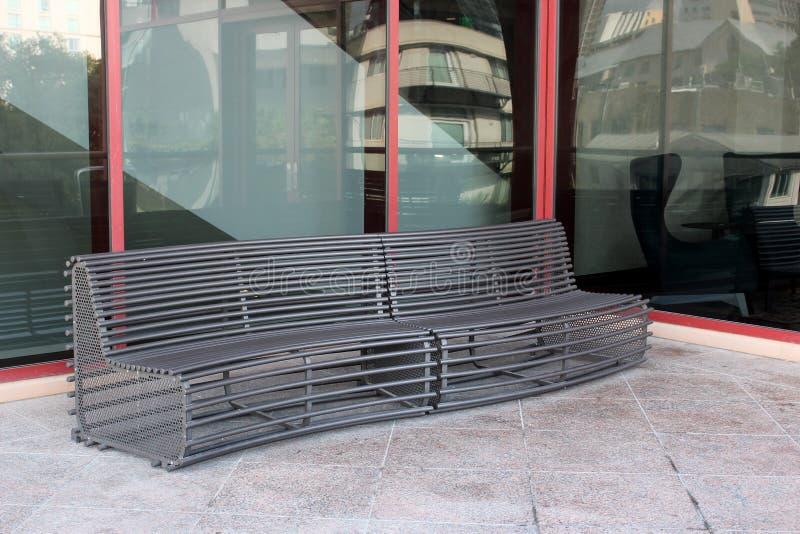 Lång buktig metallbänk för att folk ska sitta på utvändig byggnad arkivfoto