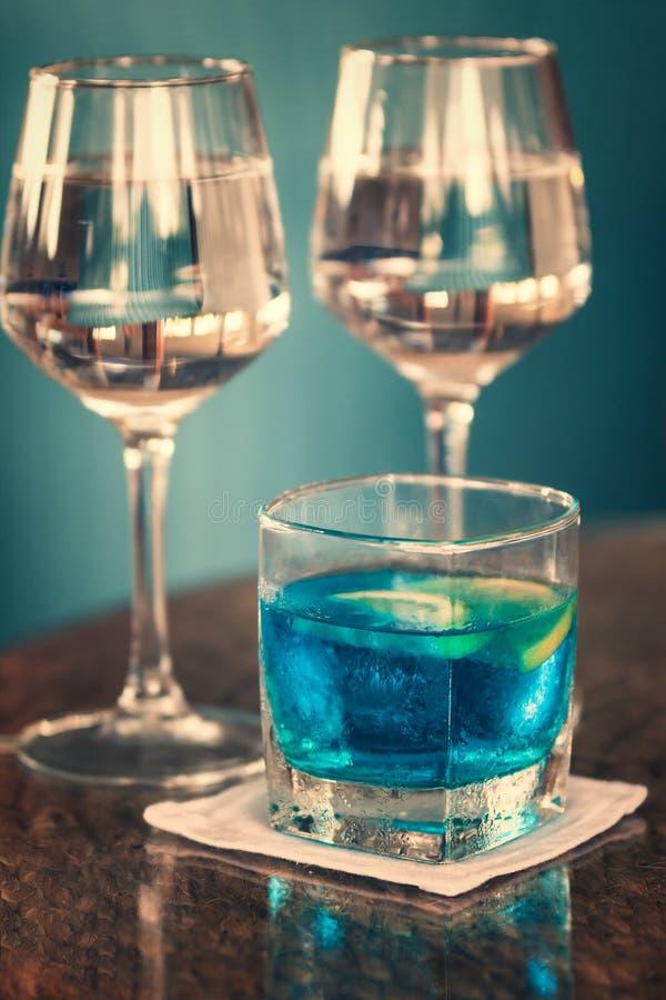 Lång drink med blåa curacao och två exponeringsglas av rosévin arkivbilder