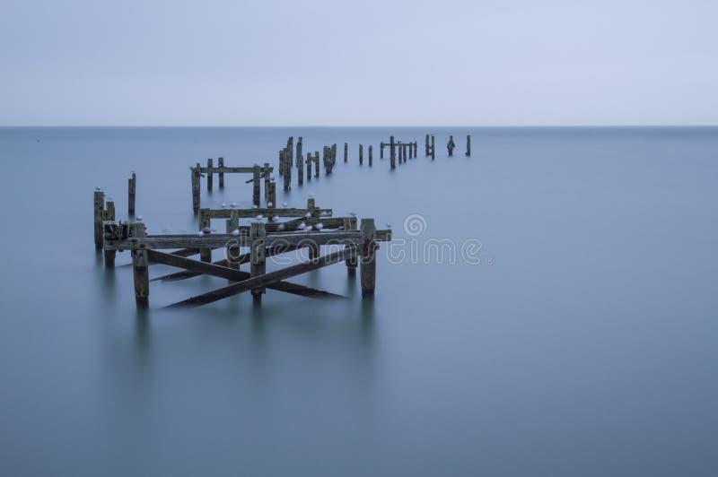 Lång exponering av den gamla pir fördärvar på slätt vatten fotografering för bildbyråer