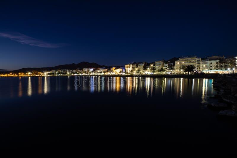 Lång exponering av en kustlinje på natten över havet med stadsljus arkivfoto