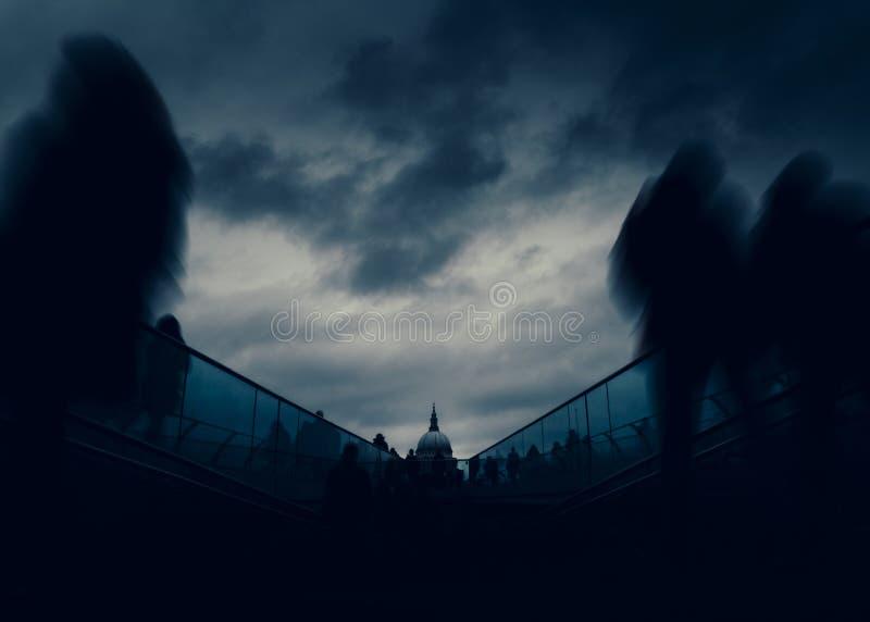 Lång exponering av gångare på London, England, UK milleniumbro med domkyrkan för St Paul ` s i bakgrund - dystopia arkivfoton