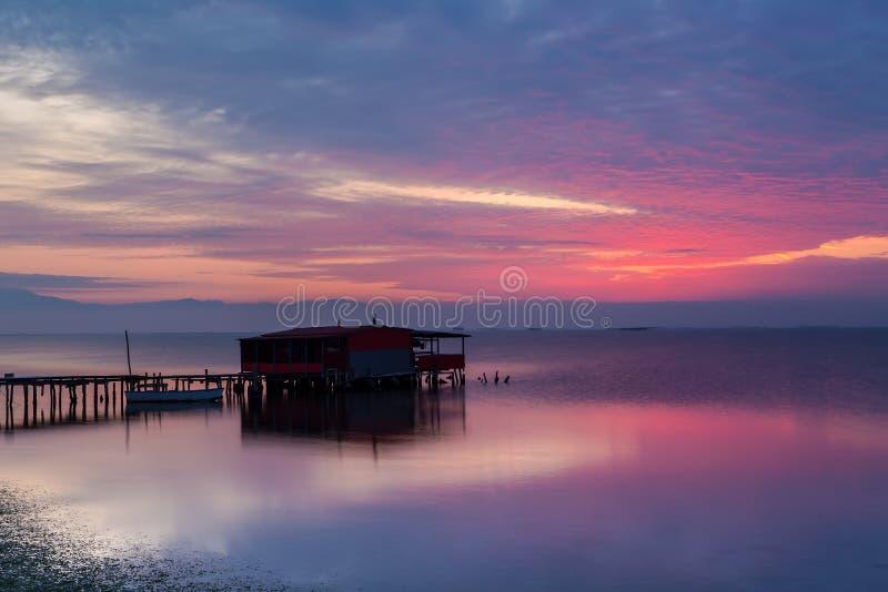 Lång exponering av magisk soluppgång över havet med en koja i royaltyfri fotografi