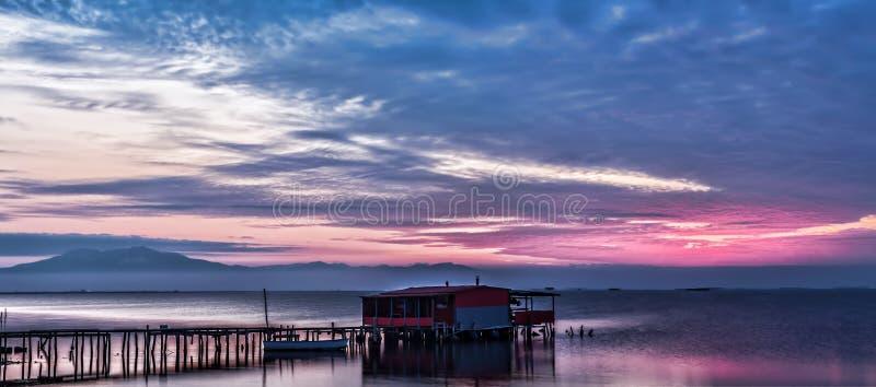 Lång exponering av magisk soluppgång över havet med en koja i arkivfoton