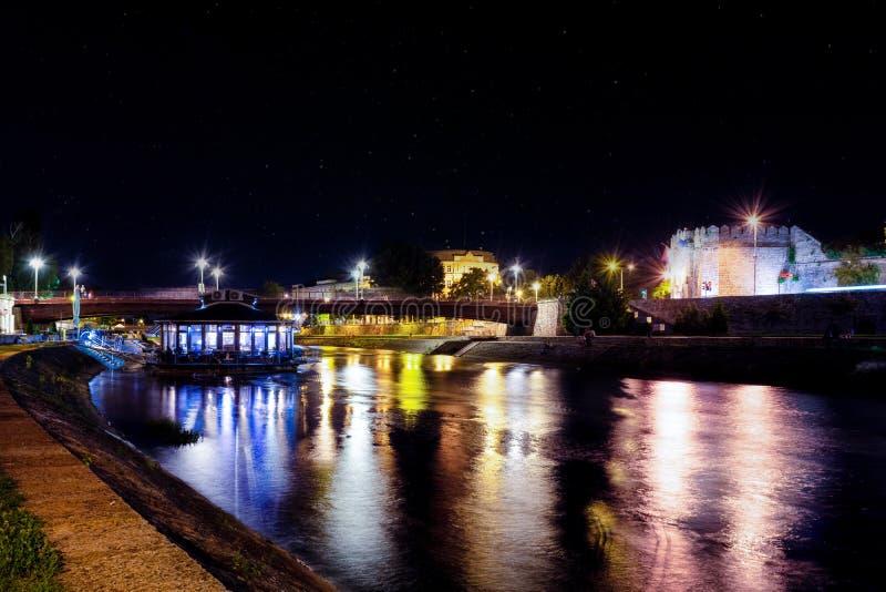Lång exponering av Nis-staden på en sommarnatt och den färgrika härliga floden Nisava med den flöterestaurangen, bron och fästnin royaltyfria bilder