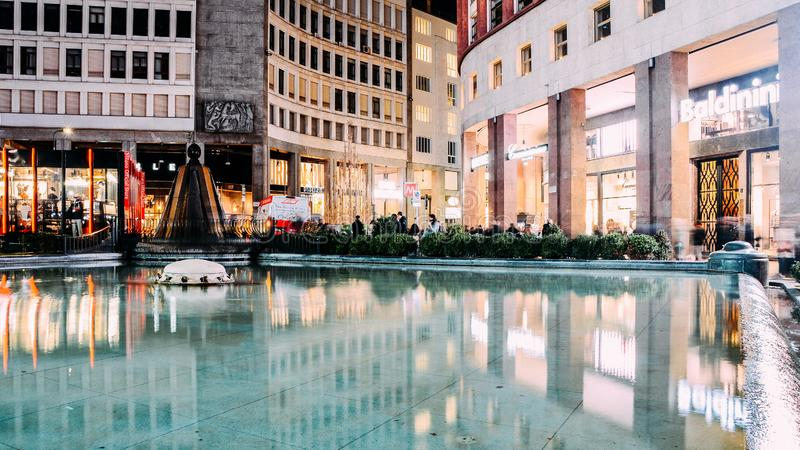 Lång exponering av shoppare på piazzaSan Babila den centrala fyrkanten med springbrunnvatten centret av Milan, Italien arkivbild