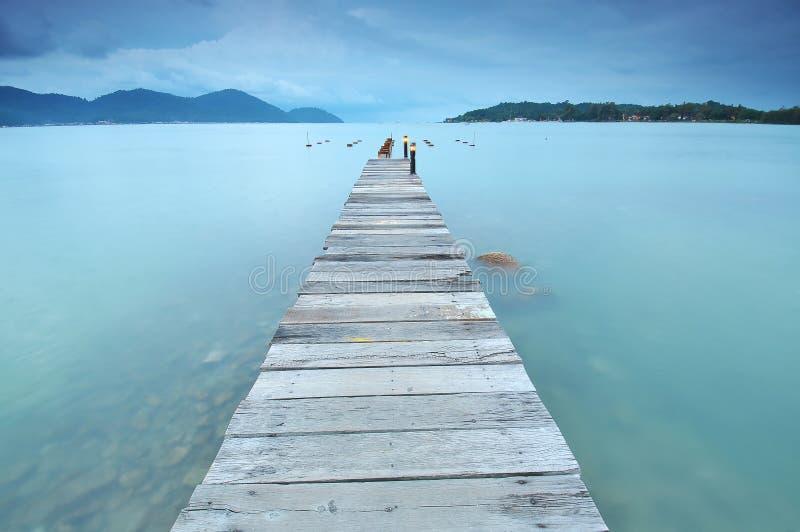 Lång exponering av träbryggan på den belägen mitt emot ön för hav med det molnet royaltyfri foto