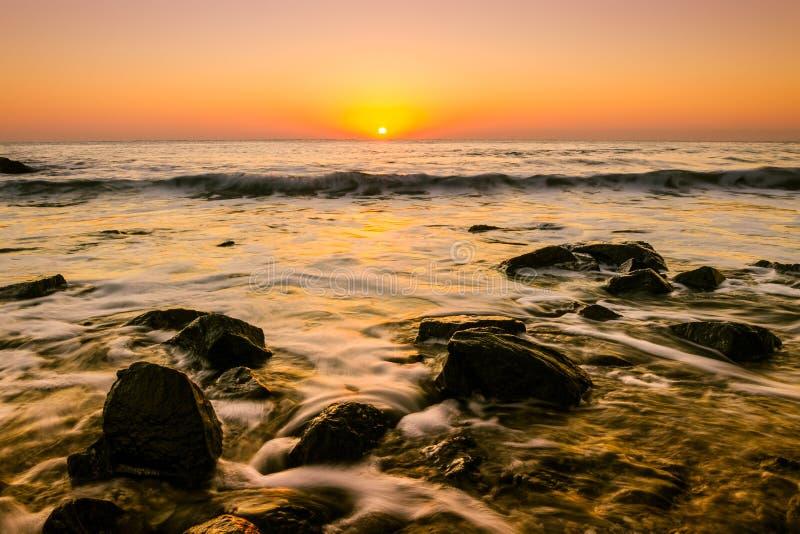 Lång exponering för Seascape på soluppgång, guld- kulört royaltyfria foton