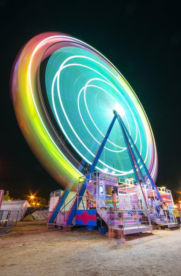 Lång exponeringsbild av ett Ferrys hjul som roterar i ett litet lokalt nöjesfält arkivbilder