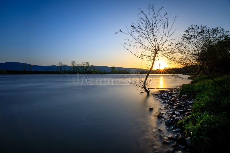 Lång exponeringssoluppgång över floden fotografering för bildbyråer