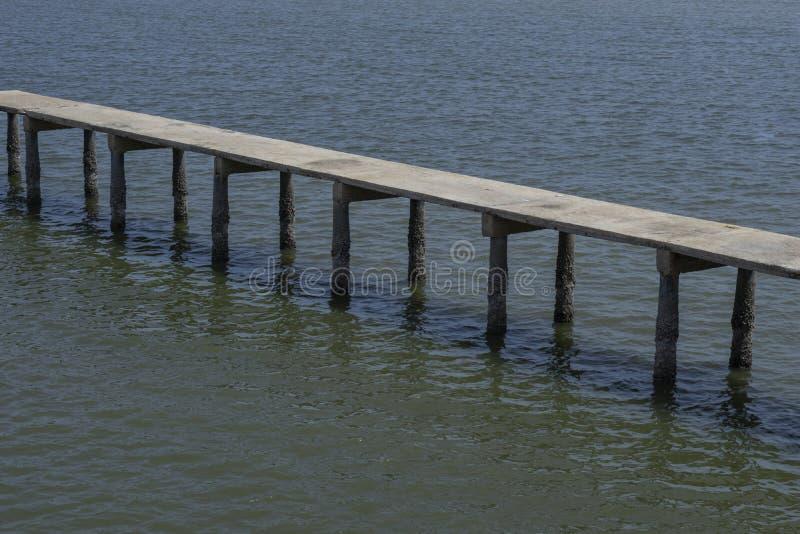 Lång gammal konkret bro över havet royaltyfri fotografi