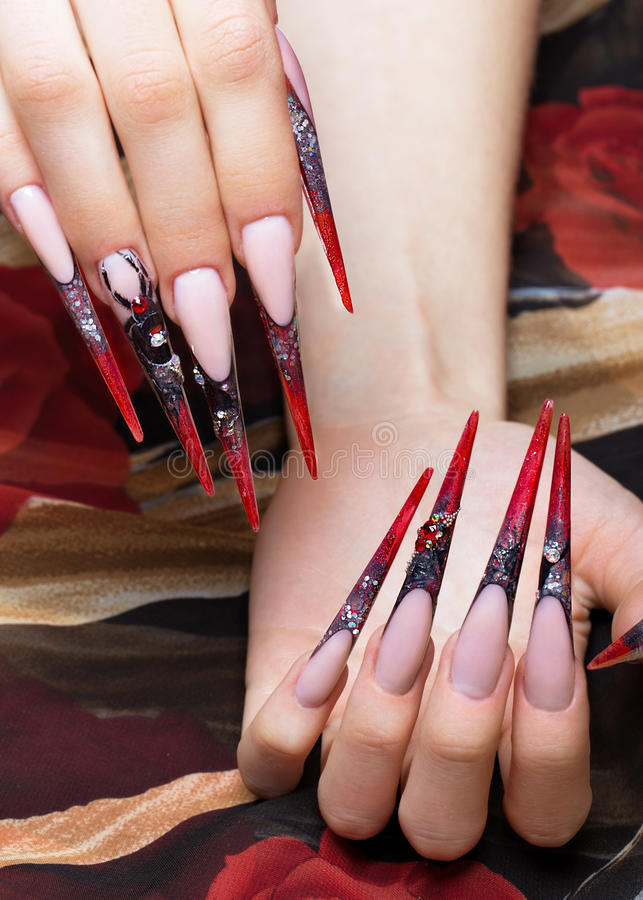 Lång härlig manikyr på fingrarna i svarta och röda färger med en spindel Spikar design Närbild royaltyfri fotografi