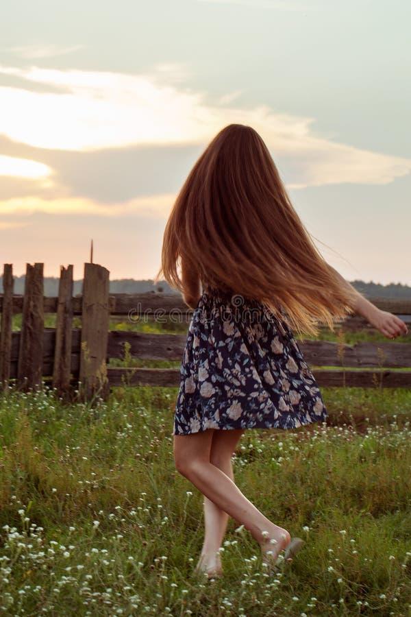 Lång hårflicka för romantisk stil i utomhus- stående för solnedgångljus royaltyfria bilder