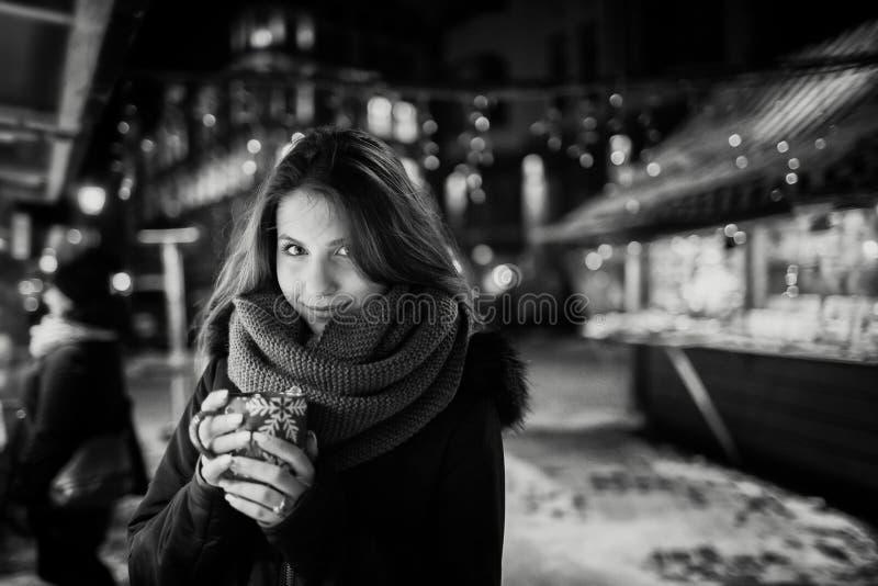 Lång hårflicka på europeisk julmarknad Ung kvinna som tycker om vintersemesterperiod Suddig ljusbakgrund, skymning Kuper wi arkivbild