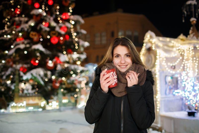 Lång hårflicka på europeisk julmarknad Ung kvinna som tycker om vintersemesterperiod Suddig ljusbakgrund, skymning Kuper wi royaltyfria foton