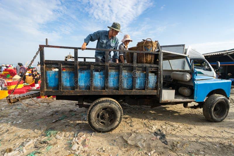 LÅNG HAI, VUNG TAU, VIETNAM - 03 JULI 2016: Män sätter korgar av fisken på lastbilen för att leverera till andra ställen till för arkivbilder