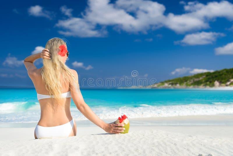 Lång haired blond kvinna med blomman i hår i bikini på den tropiska stranden fotografering för bildbyråer