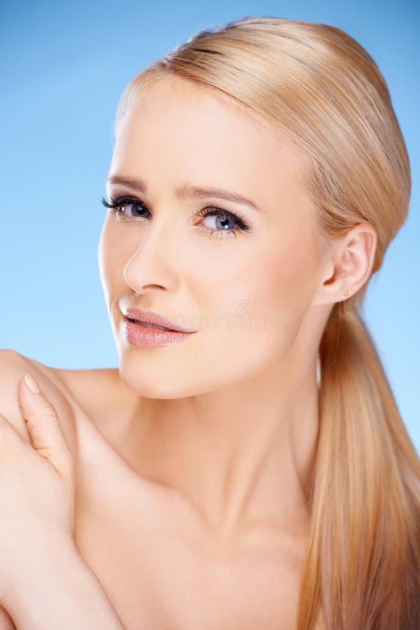 Lång haired blond kvinnastående på blått arkivfoto