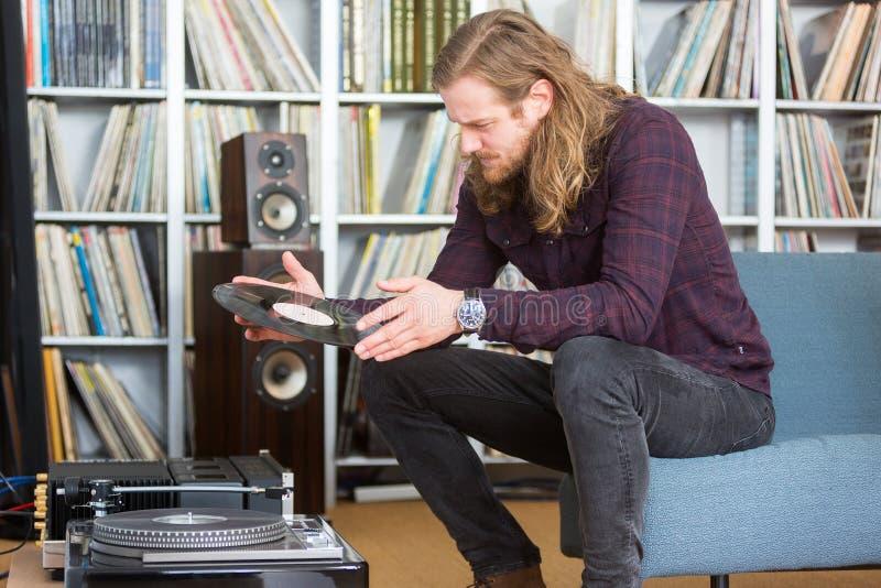 Lång haired man som sätter en vinyl på skivtallriken royaltyfri foto