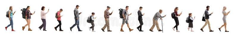 Lång kö av folk som går och använder en mobiltelefon royaltyfri foto
