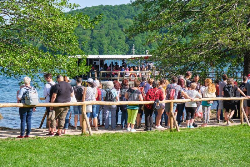 Lång kö av folk som väntar på det elektriska fartyget för att korsa Kozjak sjön Jezero Kozjak Popul?r touristic destination i Kro royaltyfria bilder