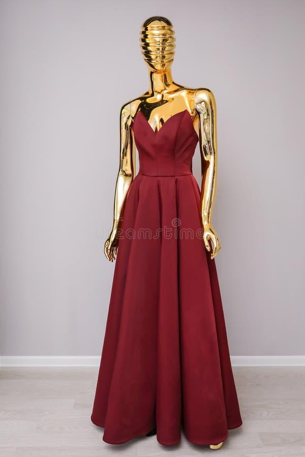 Lång klänning för Bourgognemode på guld- skyltdocka arkivbild