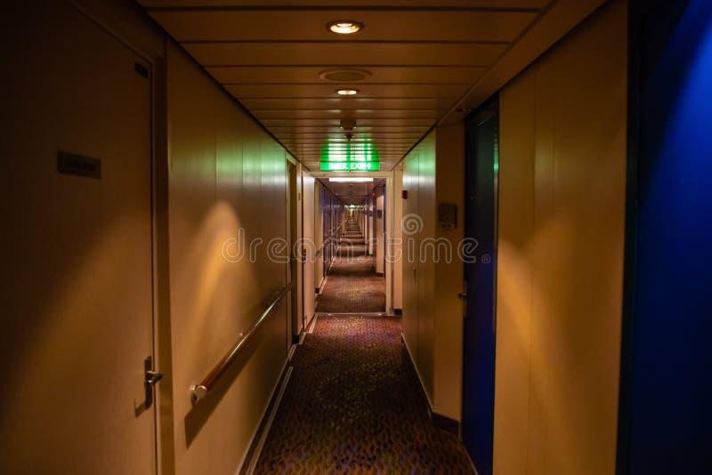 Lång korridor av kryssningskeppet, gula väggar och blåa dörrar royaltyfri bild