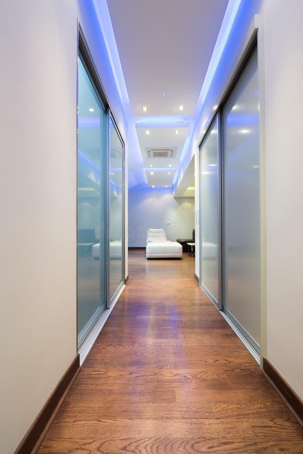 Lång korridor i lyxig lägenhet med färgrika takljus royaltyfria bilder