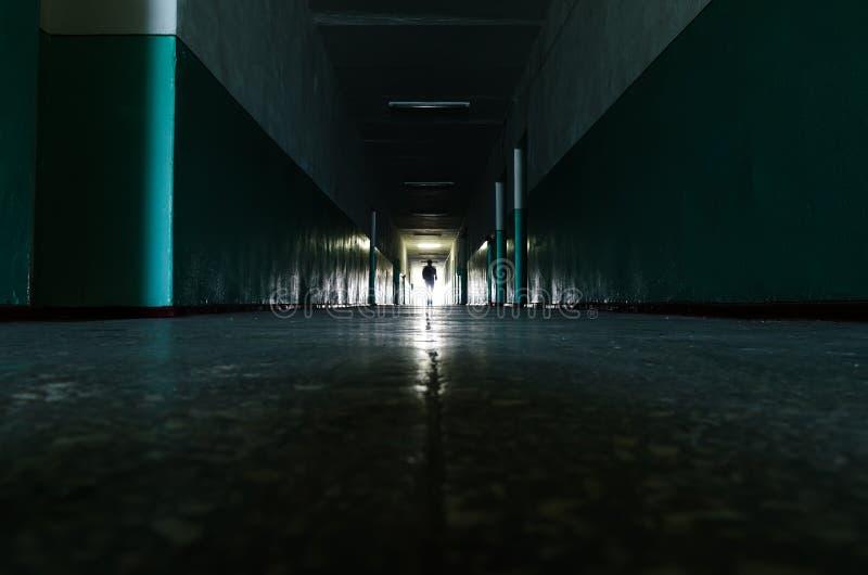 Lång mörk korridor som banan till oändligheten med människokroppen på det ljusa slutet royaltyfria bilder