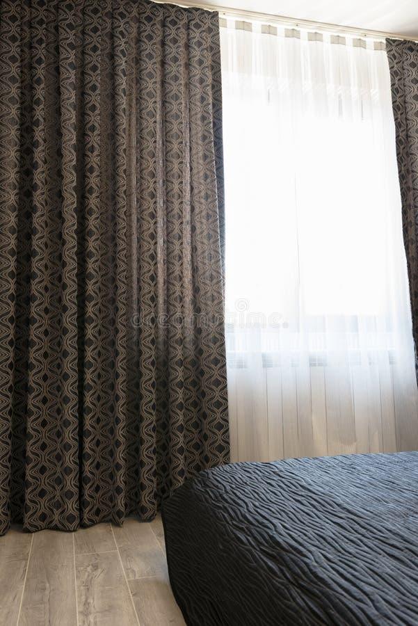 Lång mörk lyx hänger upp gardiner, och tyllen hänger upp gardiner, sax på ett fönster i sovrummet interioren för begreppsdesignen arkivfoto