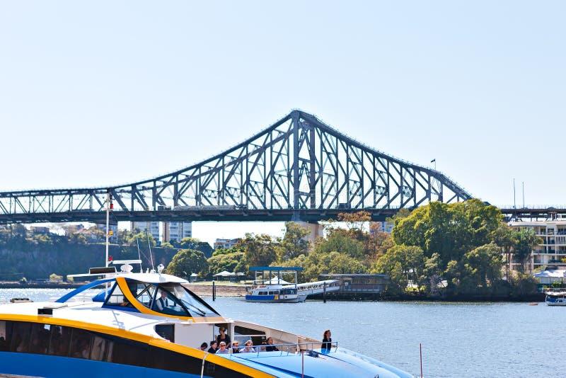 L?ng metallbro och ett fartyg p? flodvattnet arkivfoto