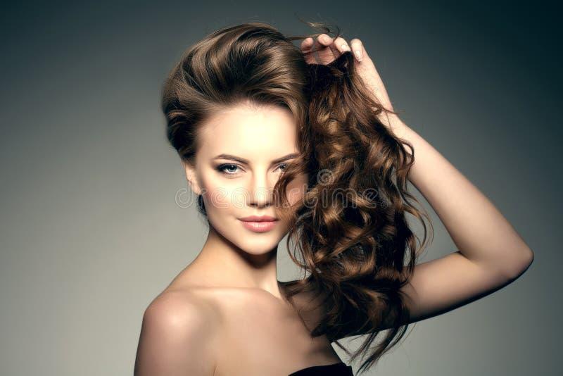 lång modell för hår Vågkrullningsfrisyr Skönhetkvinna med långt sunt och skinande slätt svart hår Updo f fotografering för bildbyråer