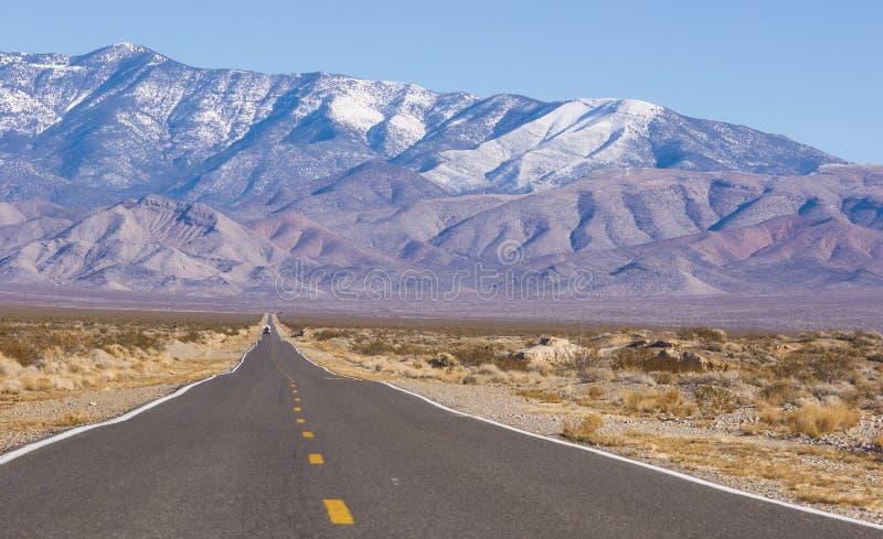 Lång och ensam väg i Mojaveöknen fotografering för bildbyråer