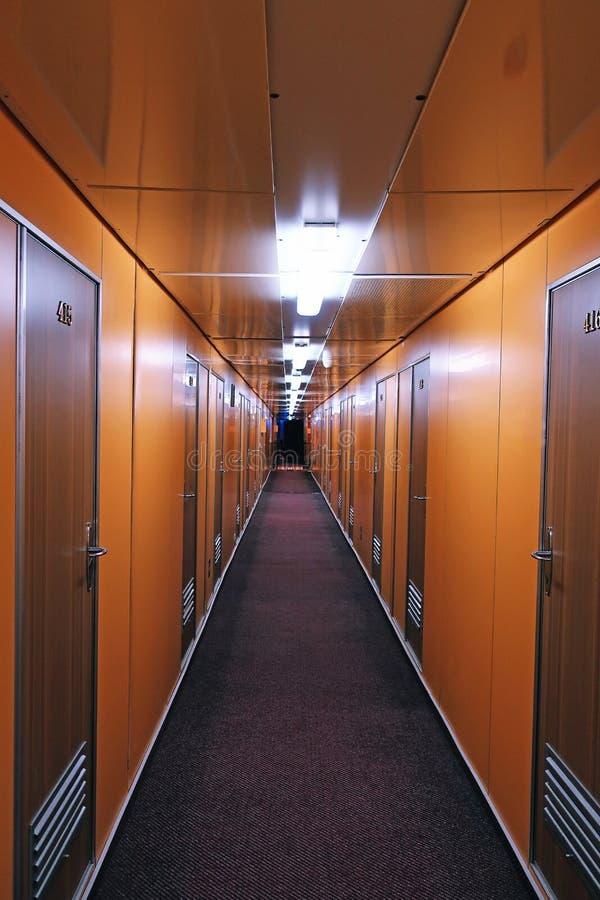 Lång orange korridor med dörrar royaltyfri bild