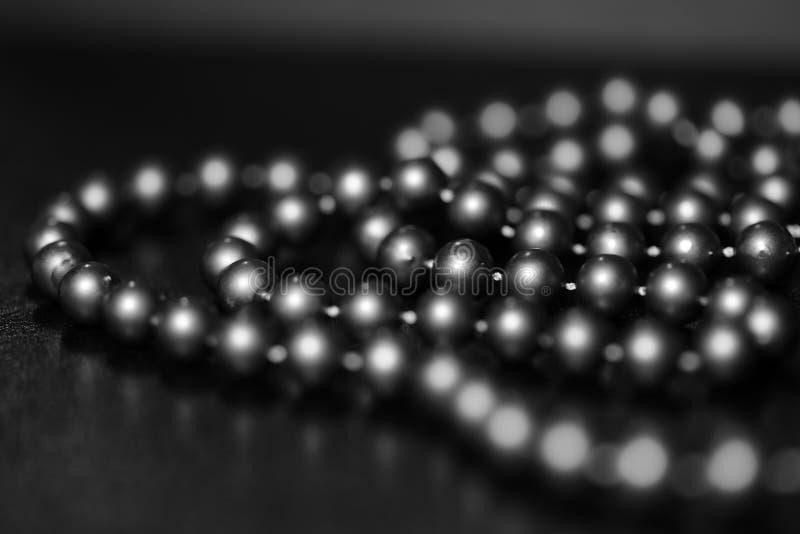 Lång prydd med pärlor halsband på en mörk bakgrund svart white royaltyfri bild